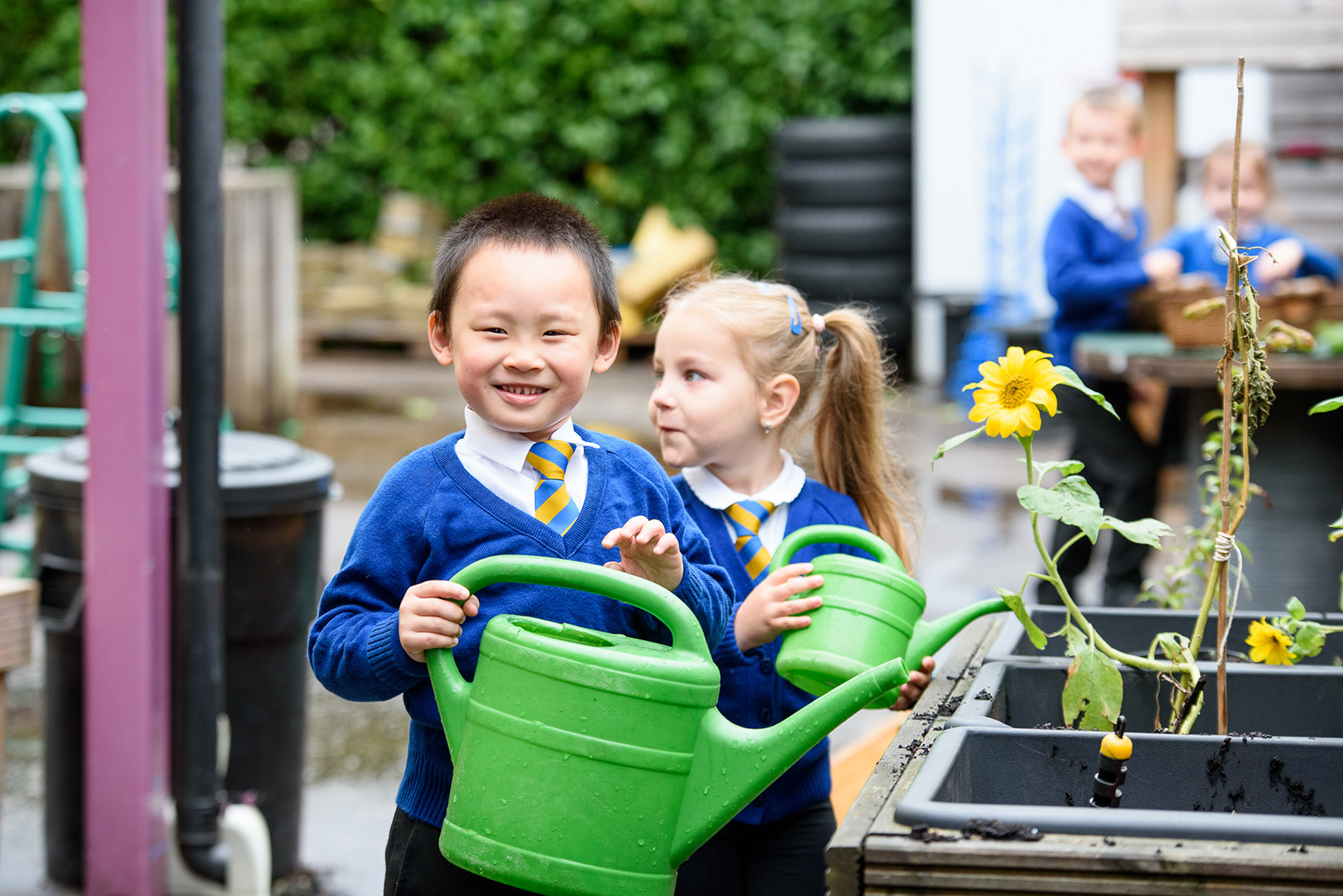 Image of children at school watering flowers